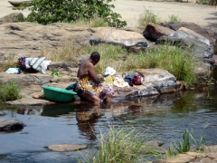 A local Kribi woman doing laundry; Lobe Waterfall