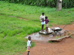 Doussala village girls pumping water at the community well