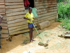 A Congolese boy shows off his home made toy, a replica of the logging truck graders that clear the roads; near Louvoulou