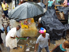 Shopkeepers brush their litter into the flooded streets; Pointe Noire