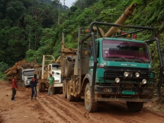 Two trucks daisy chain themselves together to pull the third one out of the muddy mess