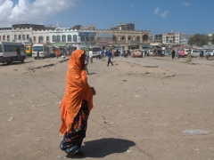 A woman crosses over the desolate parking lot of the central minibus hub; Djibouti