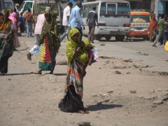 A woman covers her child for protection against the in the midday heat