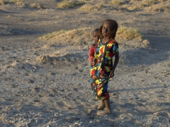 A shy Afar girl shields her brother from us. These children were tasked with watching their family's livestock; Lac Abbe