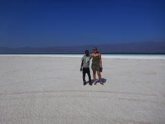 Omar and Becky standing on the salty shoreline of Lac Assal