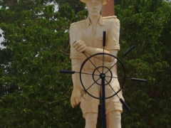A mocking statue of a Belgian explorer at a traffic roundabout in Boma