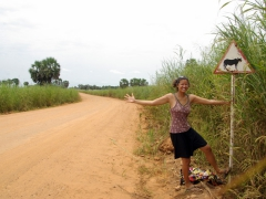 "Becky acting goofy at a ""yield to cow"" sign; DRC countryside"