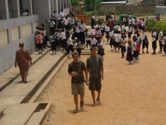 Robby and Luke walk through a throng of excited school children at the Maison D'Accueil in Matadi