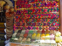 Spices for sale beneath a colorful display of table mats; Aswan Old Bazaar