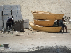 Dock workers suffer in the midday heat, seeking refuge from the sun with what little shade there is; Aswan