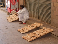 A man sits beside three trays of freshly baked bread in the early morning hours of a Ramadan day; Aswan
