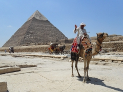 A cameleer waves a greeting with the Pyramid of Khafre in the background