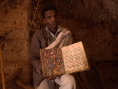 The priest holds up a bible for us to examine; Abuna Yemata Guh