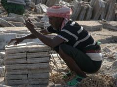 A salt worker bundles up his valuable cargo for transport by camel caravan back to Berhale or Mekele