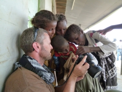Robby shows some Afar children a photo on his camera's display