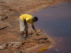 """Our driver, Yamani, pulls out a petrified duck. It mistook this lake (known locally as """"Oily Lake"""") as a freshwater source. The lake is actually a bubbling cauldron of potassium"""