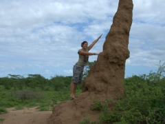 Becky stands next to a towering ant hill; outskirts of Kolcho