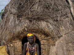 A village elder poses in the doorway to her hut; Kolcho