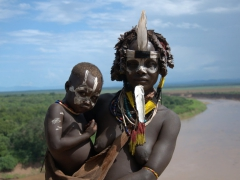A Karo mother poses with her son against a backdrop of the Omo River. The Kolcho Village is perhaps the most scenic of the Karo villages since it commands a sweeping view of the river
