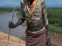 The eldest Karo tribesman clutches his stool and a walking stick