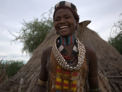 This beautiful Hamer girl is tickled pink and bursts into laughter at a private joke; Turmi
