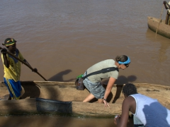 Becky precariously balances her way into a dugout canoe. This was our mode of transport across the Omo River to visit the Dasanech Tribe