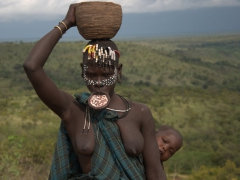 A Mursi woman strikes a pose while her curious baby pops his head out