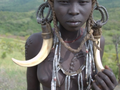 This young Mursi girl broke with tradition by refusing to get a lip plate. She does have body scarification but will be looked down upon by her fellow Mursi tribe members