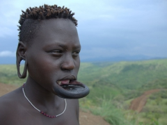 At puberty, Mursi girls have their lower teeth removed (at least 2 and sometimes 4) and their lower lip pierced to insert a lip plug. Once their lip stretches out, the lip plug gets larger and larger until a clay plate can be inserted. The larger the lip plate, the more desirable the woman to a Mursi man. Here, you can clearly see where this girl's lower teeth have been extracted