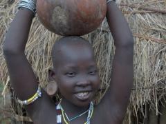 A Mursi girl balances a calabash gourd atop her head