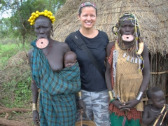 Becky poses in between two Mursi women and their children
