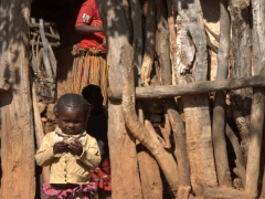 A Konso girl stands in the archway to her house in Gesergiyo