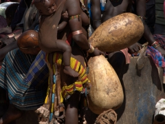 With a baby strapped to her back, a Hamer woman selects which gourd she wants to purchase; Dimeka Market