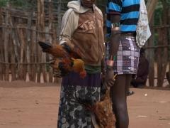 A woman examining a Banna man's chickens at the Dimeka Market