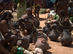 A Hamer woman examines a pot; Dimeka Market