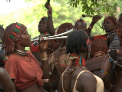 A Hamer woman blows a horn to encourage the other women to keep singing and dancing. This part of the ceremony is a riotous affair with lots of sounds, colors and excitement brewing in the air