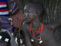 A young boy observes the face painting ritual