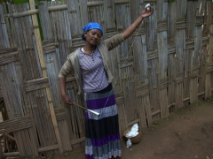 A Dorze woman demonstrates how to spin cotton using a hand spindle