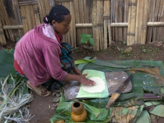 A Dorze woman prepares ensete (false banana) pancakes, a staple food for this area