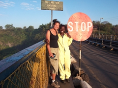 Becky stands next to a bridge guard on the Victoria Falls Bridge (the guard regulates the traffic flow on both directions of the bridge)