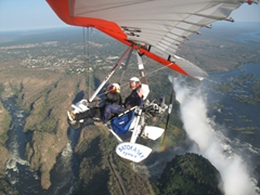 Becky waves at the camera in her microlight flight over Victoria Falls