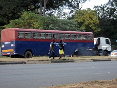 A tractor pulling the remnants of a bus; downtown Harare