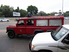 An old fashioned fire truck zooms down the streets of Harare