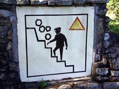 A humorous signpost warning visitors of tumbling rocks; Great Zimbabwean Ruins