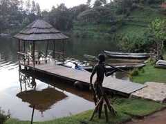 A fisherman statue stands near the jetty at the Bunyonyi Overland Resort