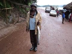 A fisherman shows of his large catfish; Lake Bunyonyi