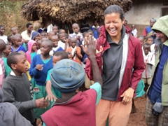 Becky laughs as she is selected to dance with her partner in the middle of the circle; Kyabahinga Orphanage