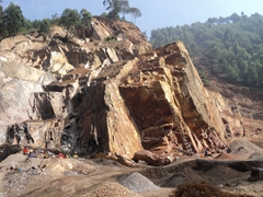 Workers perform back breaking work at a rock quarry; near Kabale