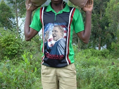 A young man wears an Obama '08 shirt while carrying a heavy sack uphill; Lake Bunyonyi