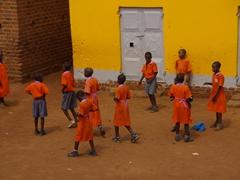 Orange clad school children on their lunch break; Kampala